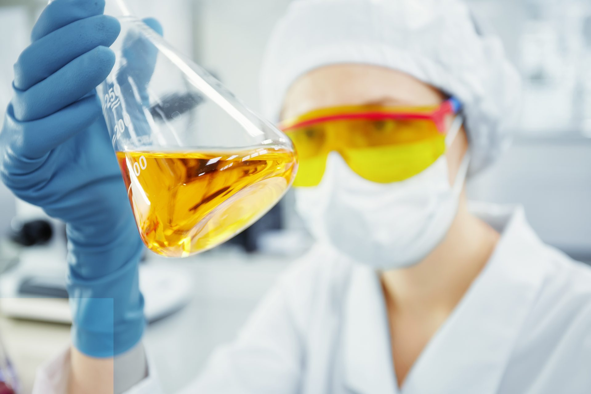 lose up portrait of young woman's hands holding test tube with yellow liquid. Medical researcher or doctor wearing surgical mask and safety glasses looking at glass tube while working in laboratory